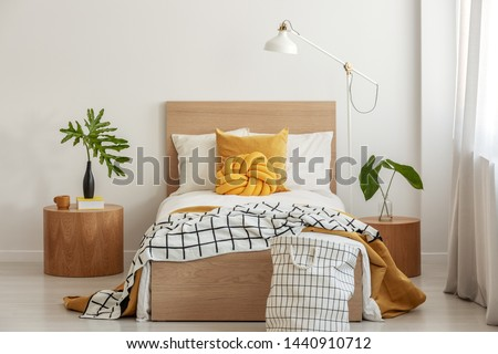 Knot pillow and black and white blanket on single bed in fashionable interior with green leaf in vase on wooden nightstand #1440910712