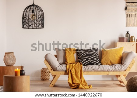 Scandinavian sofa with pillows and dark yellow blanket in bright living room interior with black chandelier #1440922670