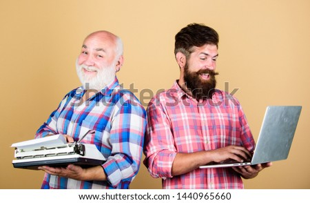 Master new technologies. Old generation. Digital technologies. Modern life and remnants of past. Senior man with typewriter and hipster with laptop. Battle of technologies. Men work writing devices. #1440965660