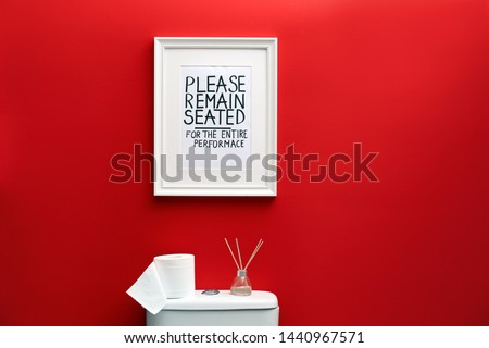 Toilet bowl and funny sign near red wall. Bathroom interior