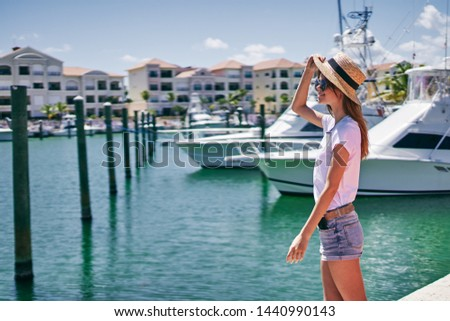 Woman in shorts and a t-shirt a hat on the head of the yacht and the boat                     #1440990143