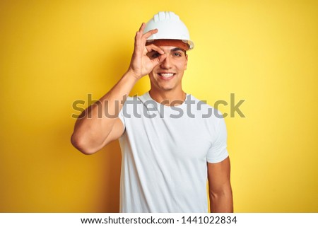 Young handsome man wearing construction helmet over yellow isolated background doing ok gesture with hand smiling, eye looking through fingers with happy face. #1441022834
