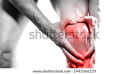 young sport man with strong athletic legs holding knee with his hands in pain after suffering ligament injury. isolated #1441066229