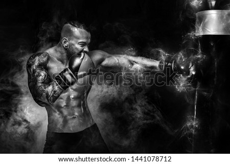 Sportsman man boxer fighting in gloves with boxing punching bag on dark background with smoke. Copy Space. Black and white photo. Royalty-Free Stock Photo #1441078712