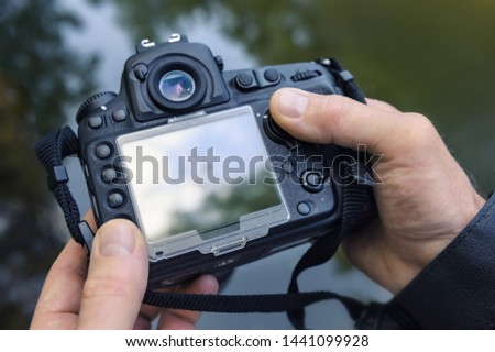 A photographer adjusts the camera. The fingers of the photographer are pushing the camera's buttons. Close-up