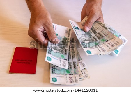 the hands of the pensioner considers bills in 1000 rubles, a pension certificate. The inscription on the certificate: 'pension certificate' #1441120811