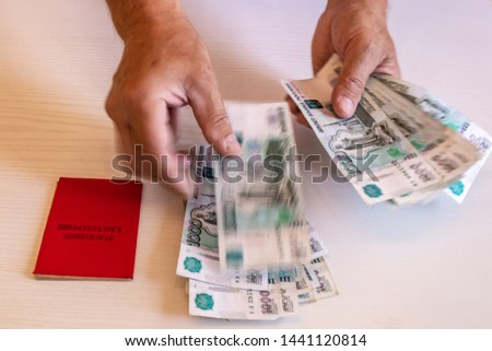 the hands of the pensioner considers bills in 1000 rubles, a pension certificate. The inscription on the certificate: 'pension certificate' #1441120814