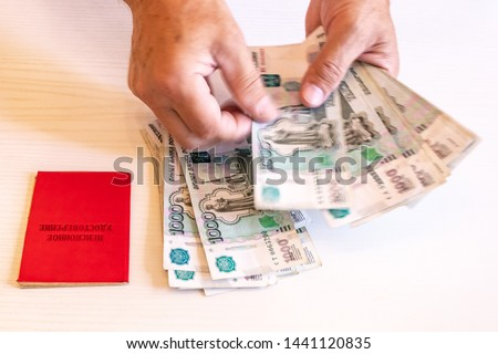 pension certificate, banknotes of 1000 rubles, the hands of a pensioner. The inscription on the certificate: 'pension certificate' #1441120835