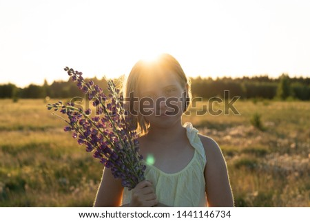 portrait of a little girl standing in a field with flowers in a yellow dress #1441146734