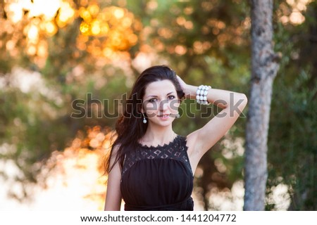Beautiful girl at sunset. Outdoor atmospheric lifestyle photo of a young beautiful lady. dark hair and eyes. Warm autumn. Warm spring. Warm summer. #1441204772