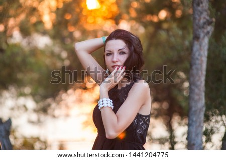 Beautiful girl at sunset. Outdoor atmospheric lifestyle photo of a young beautiful lady. dark hair and eyes. Warm autumn. Warm spring. Warm summer. #1441204775