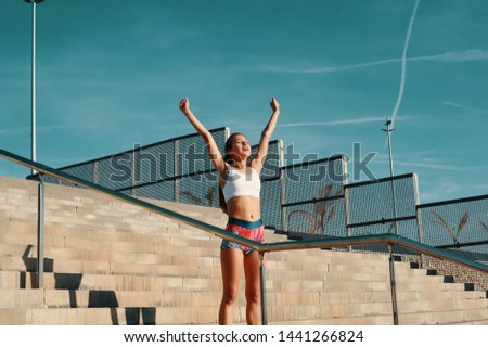 I did it! Beautiful young woman in sports clothing keeping arms outstretched while exercising outdoors #1441266824