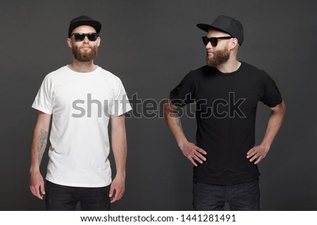 Hipster handsome male model with beard wearing black and white blank t-shirt and a baseball cap with space for your logo #1441281491
