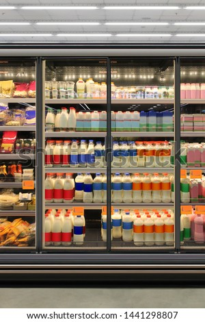Dairy product in Glass door fridge Horizontal photo mockup yogurt and milk and plastic diary bottles in vertical freezer at supermarket. Suitable for presenting new Dairy packaging or label design #1441298807