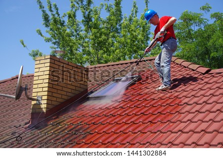 House roof cleaning with pressure tool. Worker on top of building washing tile with professional equipment. Moss removing with water. Royalty-Free Stock Photo #1441302884