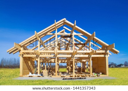 Frame house under construction. Construction site on a sunny day. House from laminated veneer timber. Remodeling of the cottage. The house wooden base. Houses to order. Production of wooden houses. #1441357343