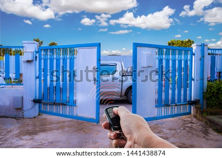 Man used hand remote control to open swing gate door by motor automation is home security system with blue cloud sky background. Royalty-Free Stock Photo #1441438874