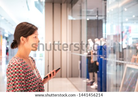 Woman using smartphone inside shopping mall #1441456214