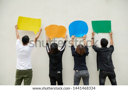 4 asian peaple holding the speech colorful paper stand in front of the white wall background, to show the ideas as comment on online communication or send the message on chat. #1441468334