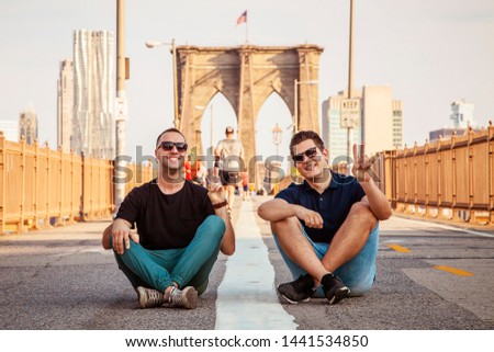Tourist handsome models wearing sunglasses posing for a photo and making peace sign on a Brooklyn Bridge with unrecognizable blurry people in background during sunny summer day In New York City, USA #1441534850