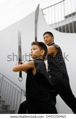 Father and son are engaged in Wushu in the city. The photo illustrates a healthy lifestyle and sport. The father trains the son. Close-up of son and father with swords. #1441550465