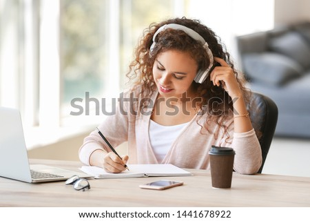 Young African-American student listening to music while preparing for exam #1441678922