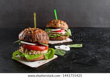 Vegetarian hamburger with tomato, lettuce, onion, bean cutlet and grain bun on dark  background. It  is an alternative to the usual hamburger.  The concept of healthy eating. Copy space. #1441755425