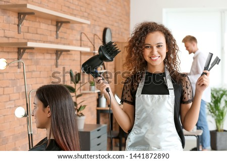Young African-American hairdresser in beauty salon Royalty-Free Stock Photo #1441872890