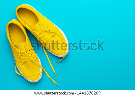 Top view photo of pair of yellow untied sneakers. Minamalist flat lay image of yellow summer footwear over blue turquoise background with copy space. Left side composition of vivid gumshoes. Royalty-Free Stock Photo #1441878209