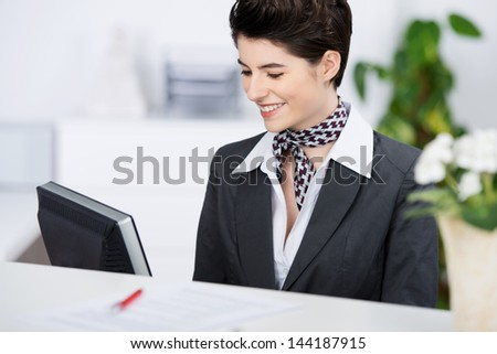 Happy young receptionist smiling while using computer at counter #144187915