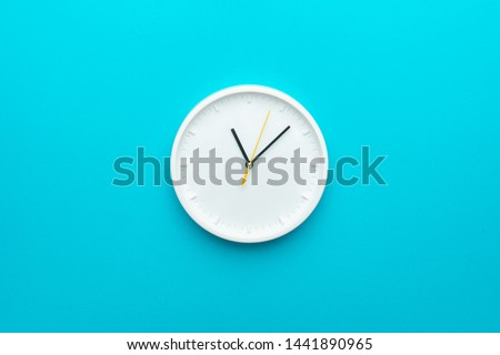 White wall clock with yellow second hand hanging on the wall. Minimalist flat lay image of plastic wall clock over blue turquiose background with copy space and central composition. #1441890965