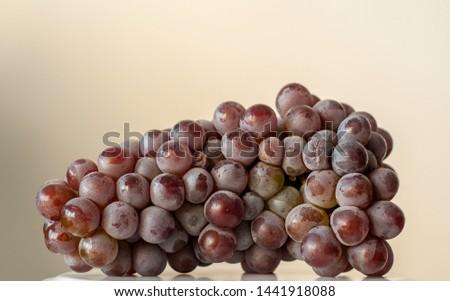 Purple grape cluster, organic grape cluster, grape cluster on beige background. #1441918088