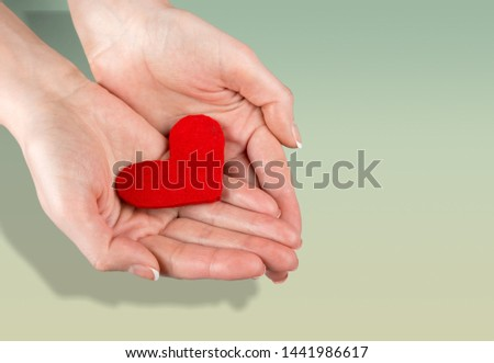 Textile red heart in woman hand on pastel background #1441986617