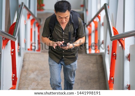 Man walking up stairs and using smartphone in city #1441998191