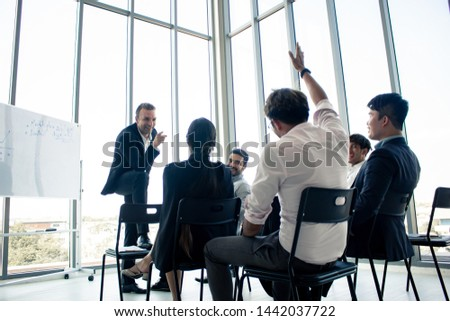 Employees raise their hands to inquire about the work in the company. Chief answers questions to those are suspected in the meeting. #1442037722