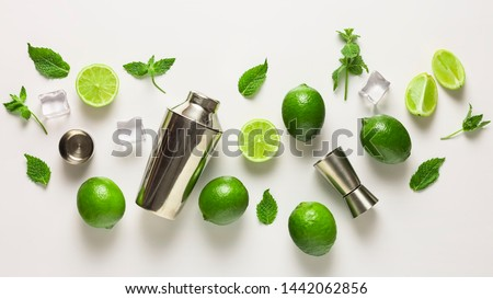 Mojito lime set, flat lay on white background. Concept: Mojito Cocktail. Whole juicy limes with ice and cocktail shaker. Concept: summer refreshing cocktail. #1442062856