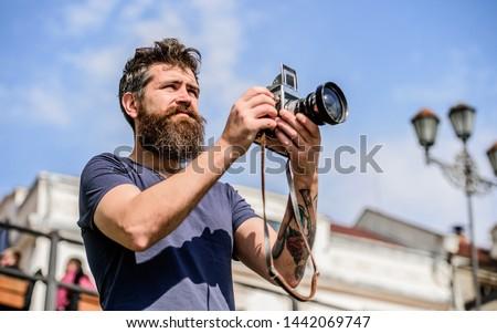 Man with long beard shooting photos. Manual settings. Photographer hold vintage camera. Modern blogger. Content creator. Man bearded hipster photographer. Photographer with beard and mustache. #1442069747