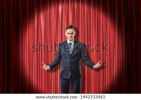 Young serious businessman with palms up on red stage curtains background. Digital art. Fame and glory. Business and commerce. #1442133443