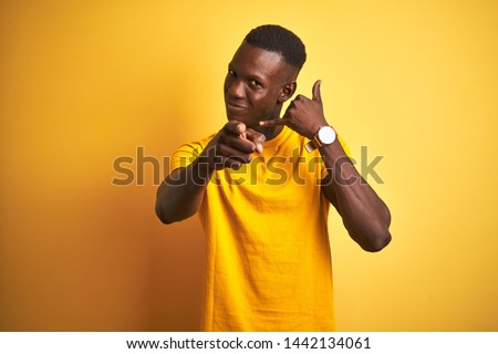 Young african american man wearing casual t-shirt standing over isolated yellow background smiling doing talking on the telephone gesture and pointing to you. Call me. Royalty-Free Stock Photo #1442134061