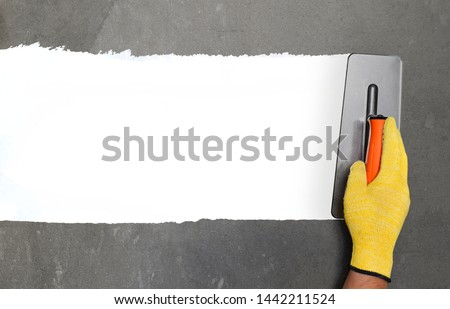 Hand with a spatula, the process of applying a layer of putty. Renovation of apartments. Repair the walls. Free space for advertising, text. #1442211524