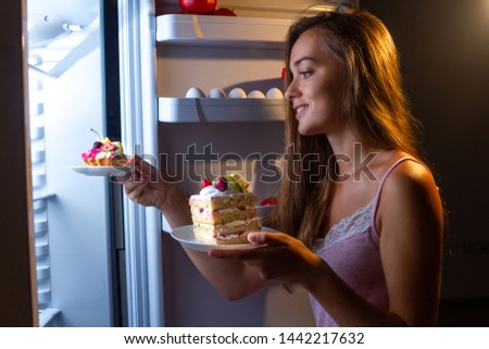 Hungry woman in pajamas eats and enjoys cakes  at night near refrigerator. Stop diet and gain extra pounds due to carbs food and unhealthy night eating  #1442217632