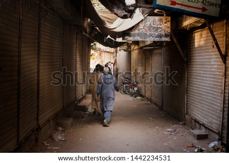 LAHORE, PAKISTAN, - November 30, 2014: Men walking home after a long day of work. #1442234531