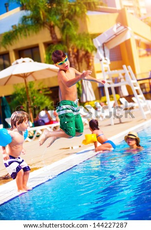 Happy family having fun in the pool, son jumping into the water, relaxed in aquapark, beach resort, summer vacation, travel and tourism concept #144227287