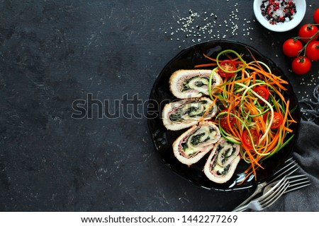 Chicken stuffed with ham, spinach and cheese served with fresh salad on dark background. Top view with copy space. #1442277269