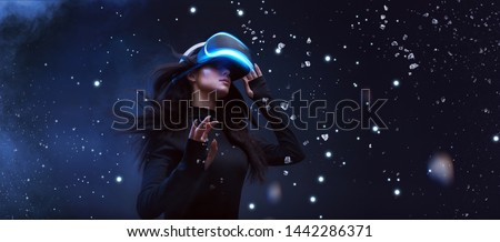 Beautiful woman with flowing hair in futuristic dress over dark background. Girl in glasses of virtual reality. Augmented reality, game, future technology concept. VR. #1442286371