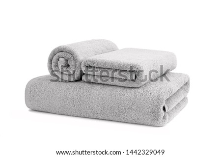 Gray terry towels rolled, folded and stacked isolated.Terry towels against white backdrop. Folded and rolled soft bath towels. Stack of grey cotton towels on a white background #1442329049