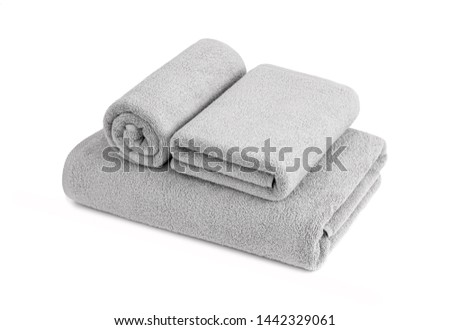 Gray terry towels rolled, folded and stacked isolated.Terry towels against white backdrop. Folded and rolled soft bath towels. Stack of grey cotton towels on a white background #1442329061