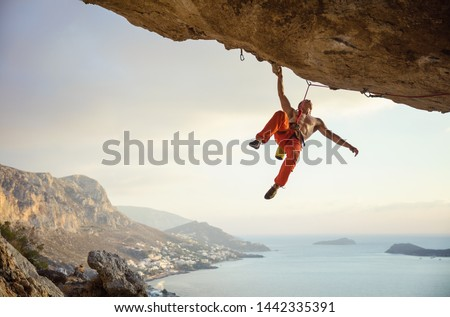 Young man climbing challenging route in cave against beautiful view of coast Royalty-Free Stock Photo #1442335391