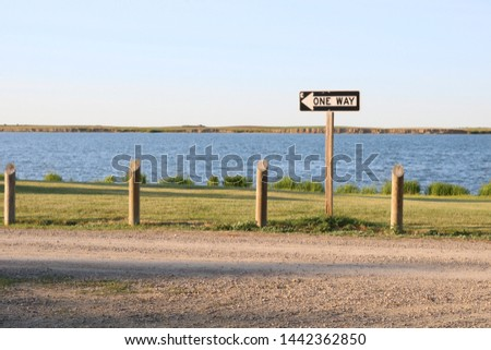 one way sign by a lake