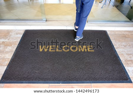 A welcome mat at the entrance of a cafe restaurant as a customer is seen entering through the front door. Royalty-Free Stock Photo #1442496173